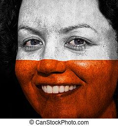 Una mujer con bandera pintada en la cara para mostrar apoyo a Polonia