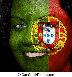 Una mujer con bandera pintada en la cara para mostrar apoyo a Portugal