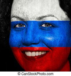 Una mujer con bandera pintada en la cara para mostrar apoyo ruso