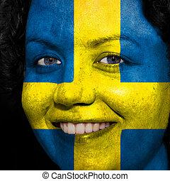 Una mujer con bandera pintada en la cara para mostrar apoyo sueco