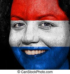 Una mujer con bandera pintada en la cara para mostrar el apoyo de Holanda