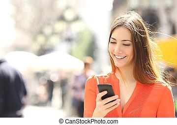 Una mujer con camisa naranja escribiendo en el teléfono inteligente