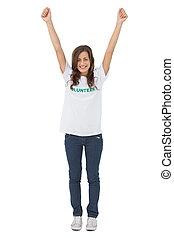 Una mujer con camiseta voluntaria levantando sus brazos