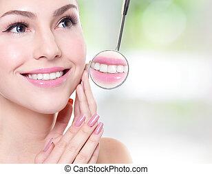 Una mujer con dientes sanos y un espejo en la boca del dentista