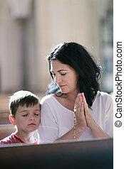 Una mujer con su hijo rezando