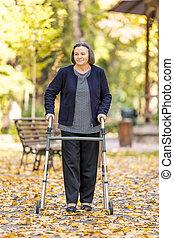 Una mujer con un caminante al aire libre en el parque de otoño