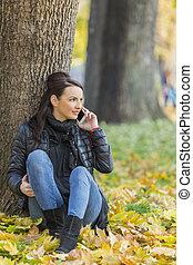 Una mujer con un móvil en un bosque en otoño