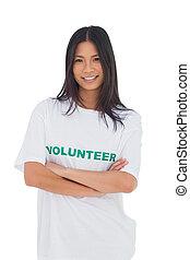 Una mujer con una camiseta voluntaria con brazos cruzados