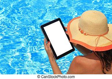 Una mujer con una tableta en la piscina