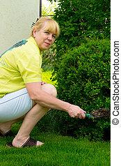 Una mujer corta los arbustos