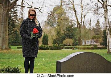 Una mujer de luto en el cementerio sosteniendo flores