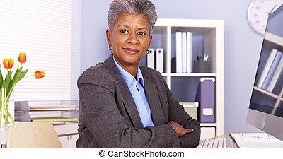 Una mujer de negocios africana sentada en el escritorio