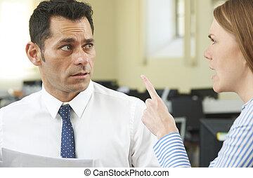 Una mujer de negocios agresiva gritándole a un colega