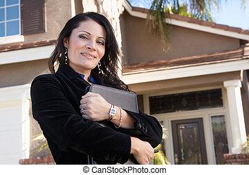 Una mujer de negocios hispana atractiva frente a un nuevo hogar
