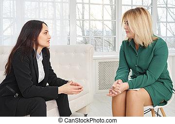 Una mujer de negocios sentada en el sofá hablando con una psicóloga