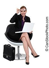 Una mujer de negocios sentada en una silla moderna.