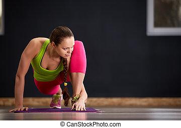 Una mujer delgada en clase de yoga haciendo hermosos ejercicios de asana. Un estilo de vida saludable en el gimnasio. Estiramiento