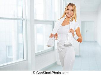 Una mujer deportiva con ropa deportiva con toalla blanca de boton