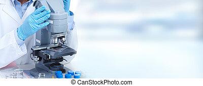 Una mujer doctora trabajando con un microscopio.