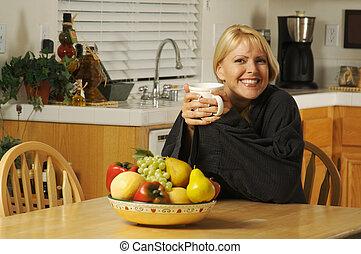 Una mujer en la cocina con una taza de café