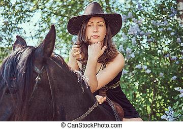 Una mujer encantadora montando un caballo marrón.