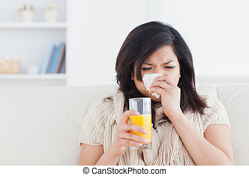 Una mujer estornudando bebiendo un vaso de jugo de naranja