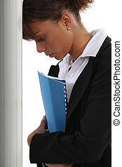 Una mujer frustrada inclinando la cabeza contra una pared