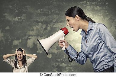 Una mujer gritando usando megáfono a una mujer estresada