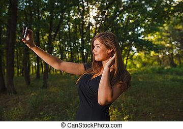 Una mujer haciéndose fotos por teléfono