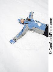 Una mujer haciendo ángel de la nieve.