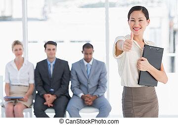 Una mujer haciendo gestos con gente esperando una entrevista