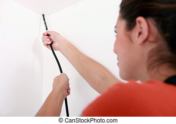 Una mujer instalando cables