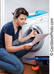 Una mujer intentando reparar la lavadora