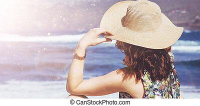 Una mujer joven y relajada mirando el océano
