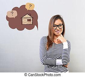 Una mujer latina de negocios feliz con gafas mirando la casa de ilustraciones en una nube de burbujas con preguntas. El concepto de protección de seguros, inversión de dinero de seguridad.