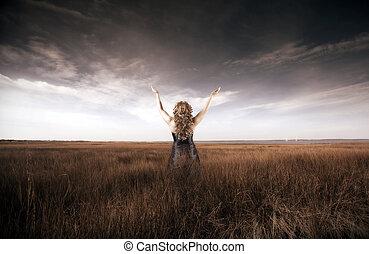Una mujer levantando las manos en un campo