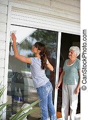 Una mujer limpiando una puerta de cristal para una anciana