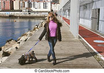 Una mujer paseando al perro