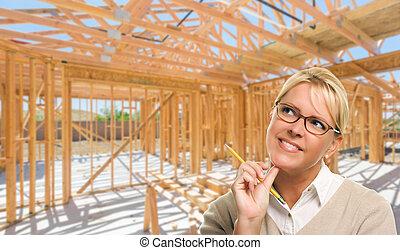 Una mujer pensativa con lápiz en el sitio dentro de la construcción de una nueva casa.