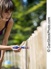 Una mujer pintando una valla de jardín