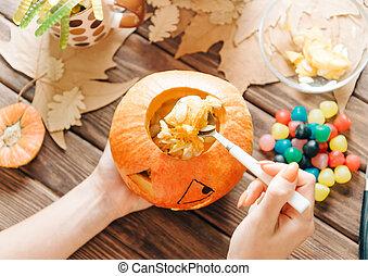 Una mujer preparando calabaza de calabaza para Halloween.