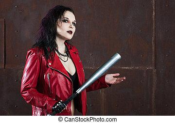 Una mujer punk agresiva con un bate, con chaqueta de cuero roja