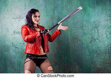 Una mujer punk agresiva golpea a alguien con un bate, con chaqueta de cuero roja