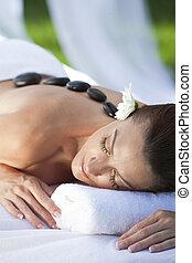 Una mujer que se relaja en el gimnasio con un masaje de piedra caliente