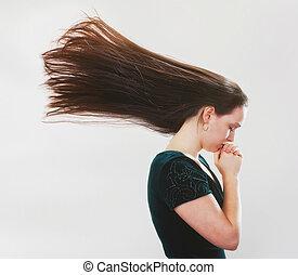 Una mujer rezando con pelo volador.