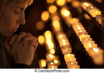 Una mujer rezando en la iglesia católica