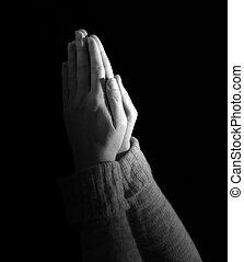 Una mujer rezando sobre el fondo negro