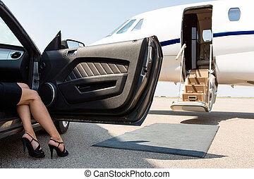 Una mujer rica saliendo del coche en la terminal
