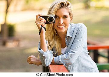 Una mujer rubia tomando fotos