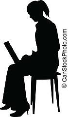 Una mujer sentada con un cuaderno